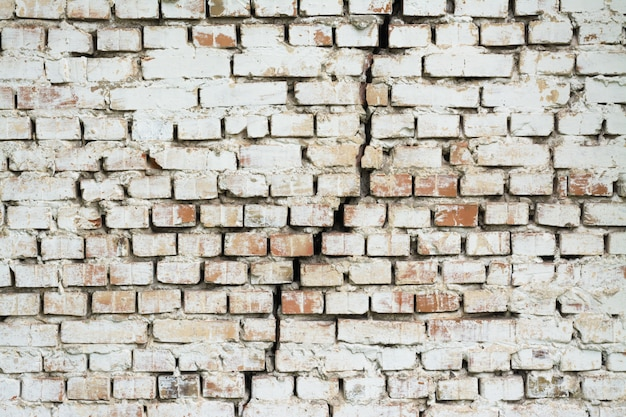 中央に大きな亀裂のあるレンガの壁。赤レンガで作られ、白いインクで塗られた壁が垂直に割れた背景