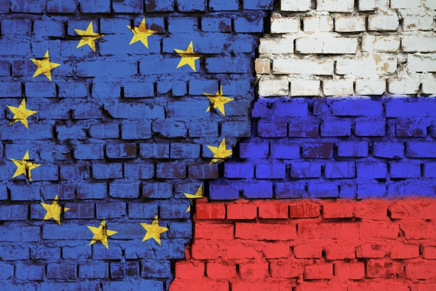 Флаги евросоюза и россии на кирпичной стене с большой трещиной в середине. символ проблем между страной и союзом