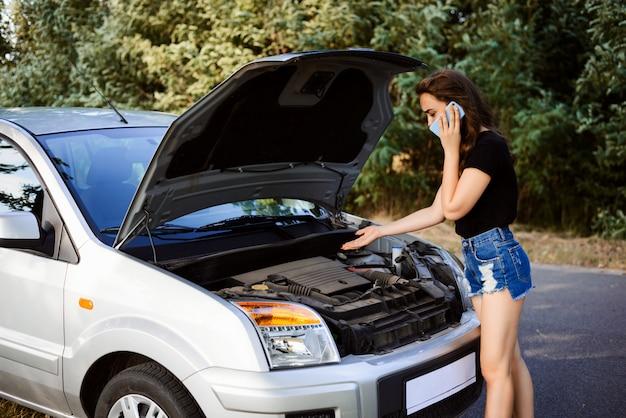 Неопытная девушка звонит друзьям, чтобы получить совет, как починить сломанную машину на дороге и добраться до дома, объясняет им, что случилось
