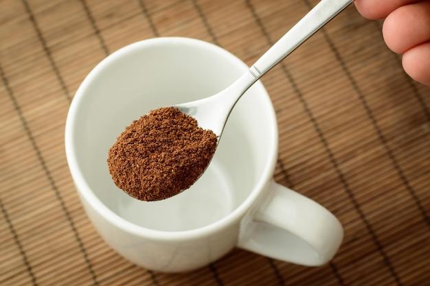 空のカップに男の手でインスタントコーヒーを入れたスプーン。コーヒーを作る
