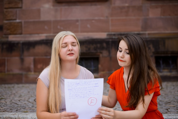 Неудачный тест. взволнованная и грустная студентка сидит с окончательным результатом теста