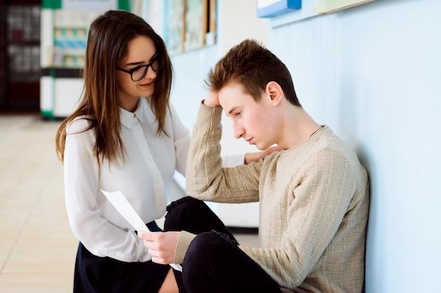 悲しい男子学生が壁の近くに座ってテストを見下ろして学業成績が悪い