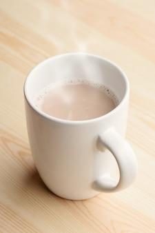 ホットチョコレートのカップは木製のテーブルの上に立つ