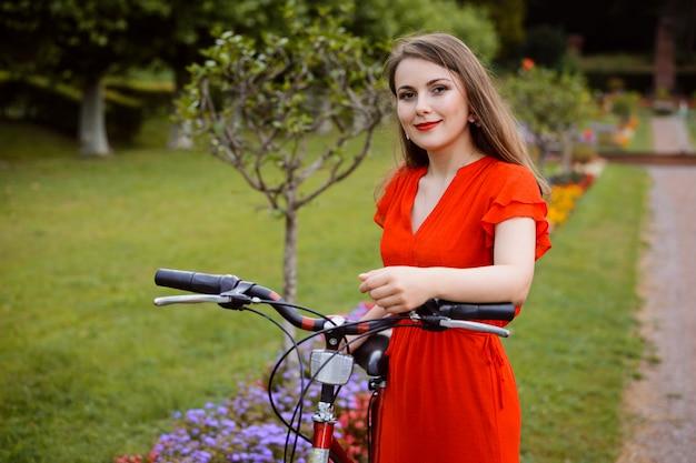 公園-赤いドレスを着た美しい少女の屋外のポートレートで自転車を持つ若い女性