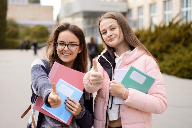 Счастливые улыбающиеся студенты обычного университета, стоя в кампусе, показывая пальцы вверх на камеру
