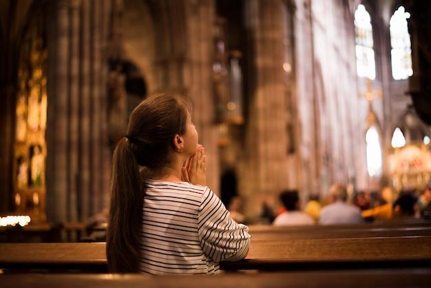 Молодая девушка молится в церкви, стоя на коленях