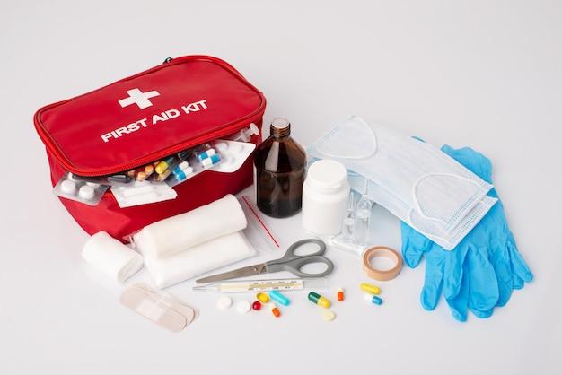 Аптечка первой помощи на белом столе. полный набор неотложной медицинской помощи, лекарства для оказания первой помощи больному или травмированному человеку на белом фоне
