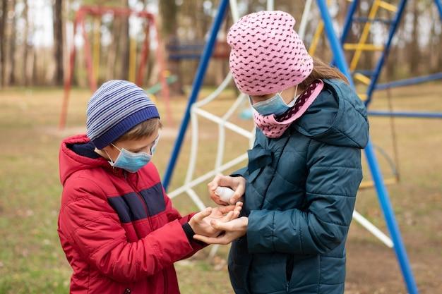 小さな女の子と男の子が遊び場で遊んでいる間手の消毒剤を使用しています。コロナウイルス流行時の手指消毒