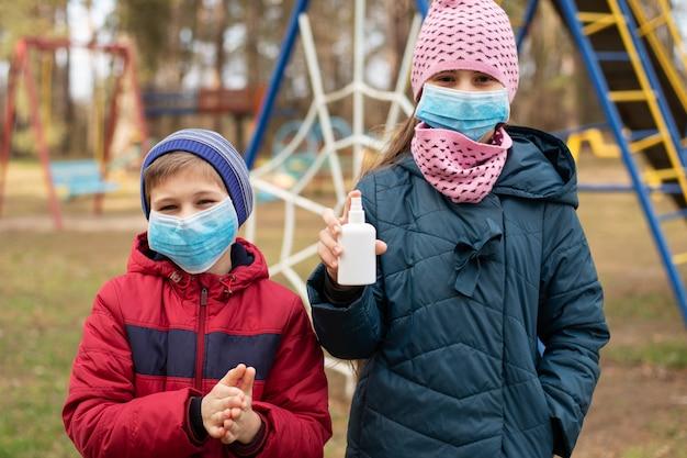 屋外の遊び場で遊んでいる間手の消毒剤を使用して医療マスクの子供。コロナウイルス検疫中の生活