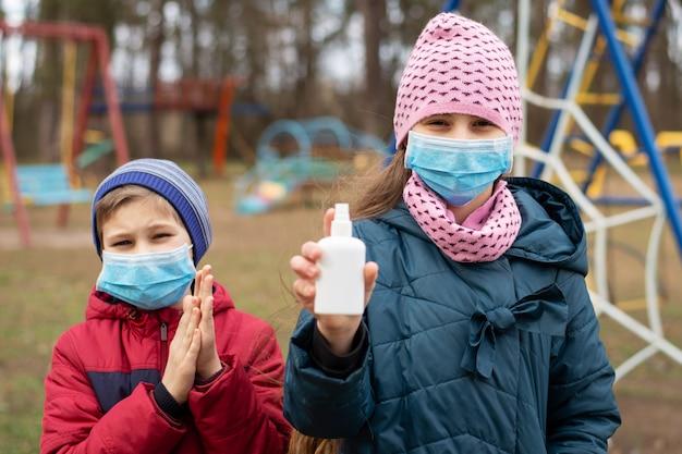 抗菌ハンドスプレーを使用して屋外でプレイしながら手を清潔に保つ慎重な少年と少女