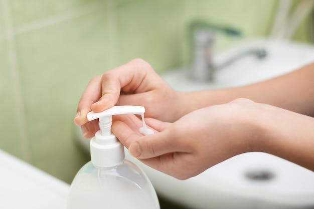Школьница принимает мыло, чтобы вымыть руки после возвращения домой. молодая девушка дезинфицирует руки после возвращения домой