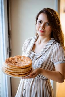 Молодая девушка держит тарелку с хлебом хачапури