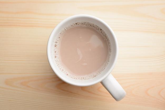 Чашка горячего какао с молоком стоит на деревянный стол