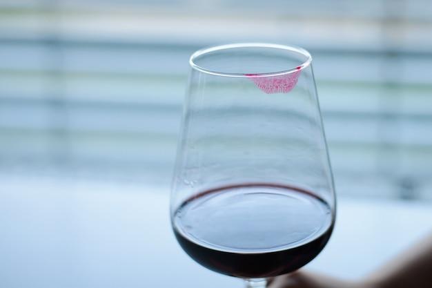 赤の女性の口紅とワインのグラス
