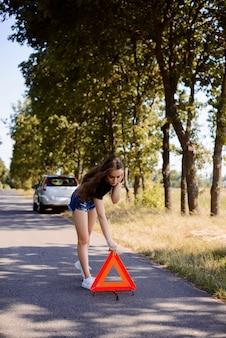 少女が田舎で車のクラッシュ後に赤い三角形の一時停止の標識を配置します。