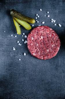 黒の背景に赤ハンバーガー肉のクローズアップ