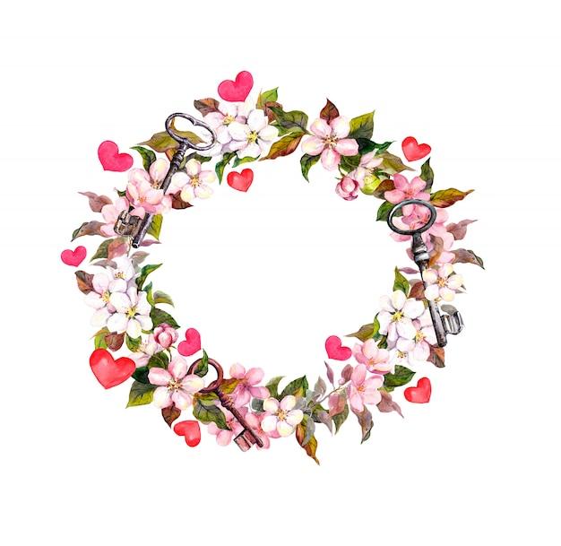 ピンクの花、羽、ハート、キーと花の花輪。バレンタインの日、結婚式の水彩サークルフレーム