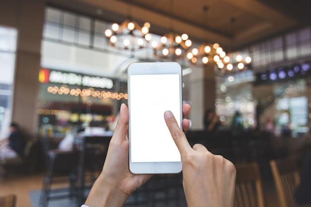 背景のコーヒーショップでぼやけた画像でスマートフォンを使用して手