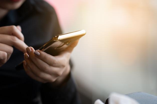 ビジネスの女性スマートフォンを使用してメッセージや電子メールを送信する