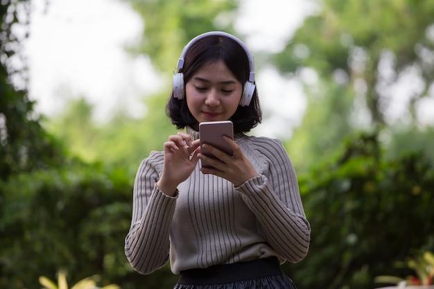 幸せなアジアの女の子たちは公園で音楽を聴いています。