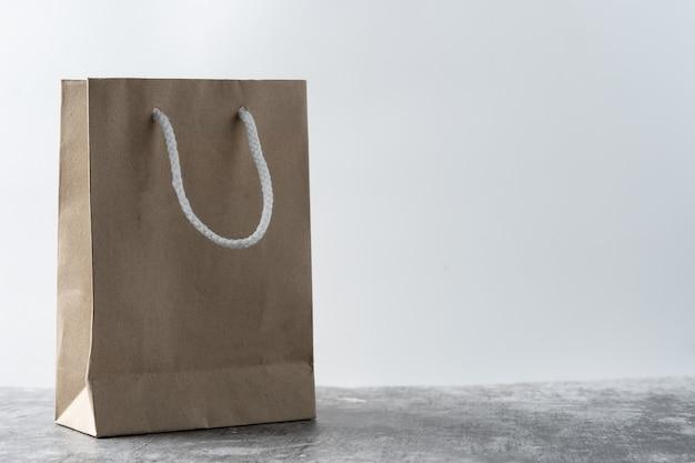 紙袋をコンクリートの床に置いた。ビニール袋発売世界を救うために