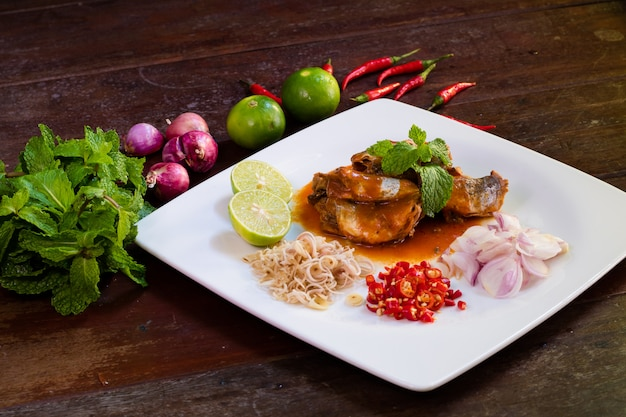 Острые рыбные консервы салат из сардины на деревянном столе
