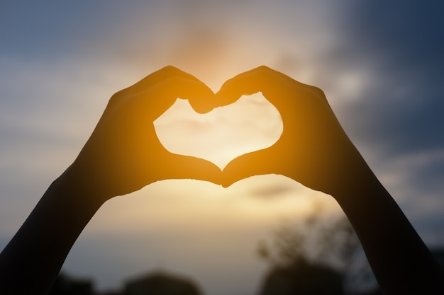 Человеческие руки в форме сердца, обрамление в закат