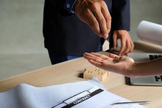 代理店は契約の署名と顧客に家の鍵リングを与えます