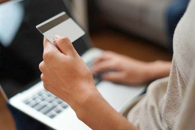 女性はオンラインショッピングと支払いにコンピューターでクレジットカードを保持しています。