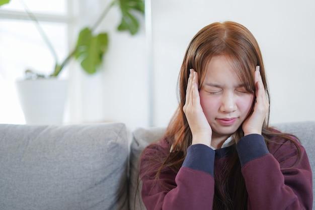 若い女性はソファの上に座る病気や頭痛を感じる