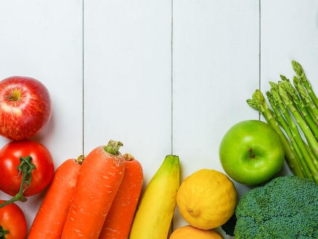 白い木製のテーブル背景に多くの果物と野菜のカラフルです