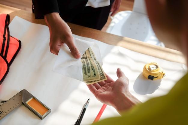労働者と従業員にお金やボーナスを払いながら両手をクローズアップ。