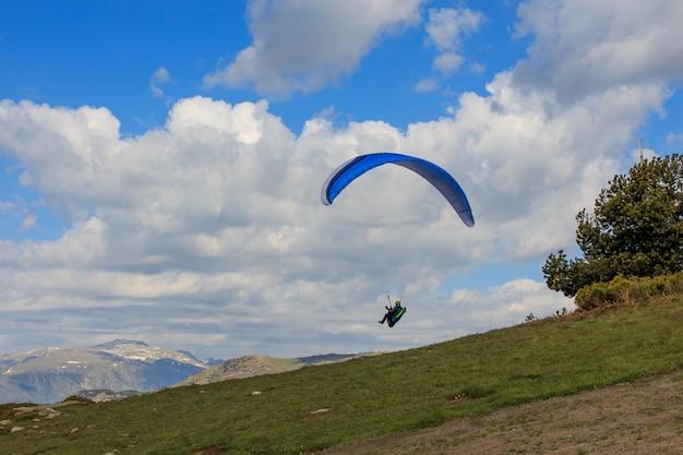 緑の牧草地を飛行するパラグライダー。スポーツコンセプト