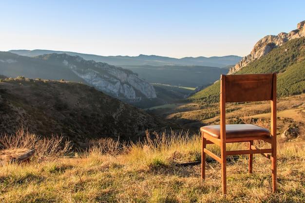 山の景色を望む山の頂上の木製の椅子