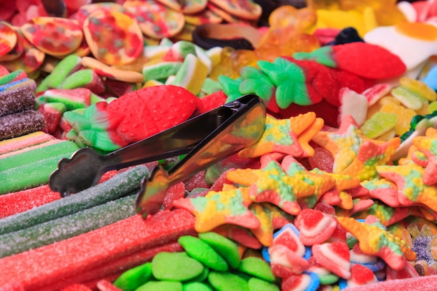 金属トングで砂糖を詰めた子供向けのさまざまな種類のジェリービーンズとキャンディーストリップ。食品のコンセプト