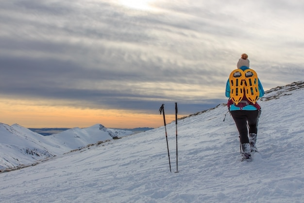 雪の山でバックパックを持つ少女。ライフスタイルのコンセプト