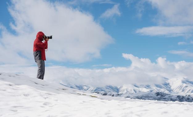 冬の山の景色と雪の上の写真を撮る男