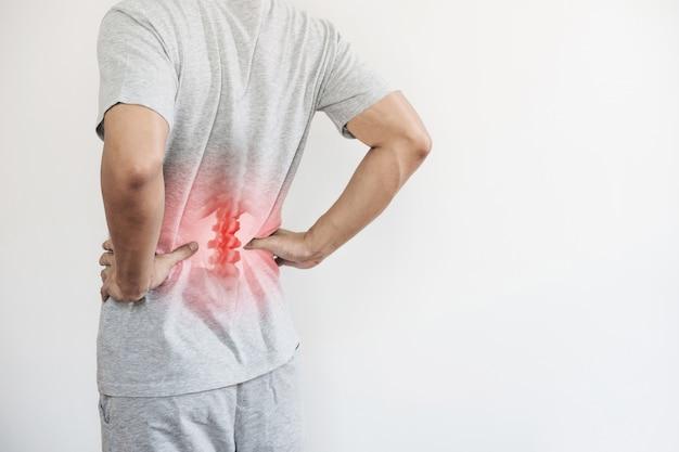 オフィス症候群、腰痛、腰痛の概念。痛みのポイントで腰に触れる男