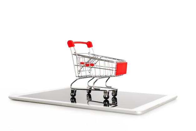 デジタルタブレット、白で隔離されるの空っぽのショッピングカート