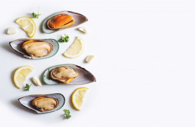 ニュージーランドのムール貝とレモン、パセリ、ニンニクのスライス、白いテーブルの上