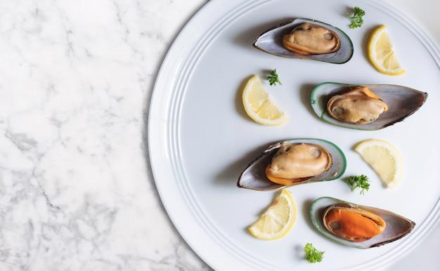 ニュージーランド産ムール貝とレモンとパセリのスライス、白い皿と白い大理石のテーブルトップ