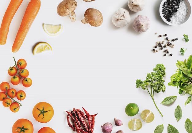 健康食品成分の背景。ハーブとスパイス、センターコピースペースと白い背景の上の有機野菜