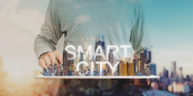 Умный город технологий, человек с помощью цифрового планшета и голограмма современных зданий