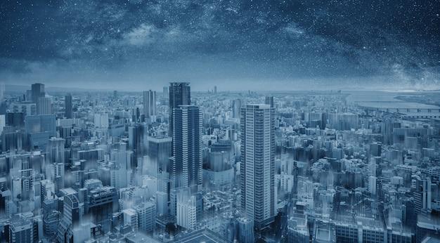 夜、星空に未来的な青いスマートシティ
