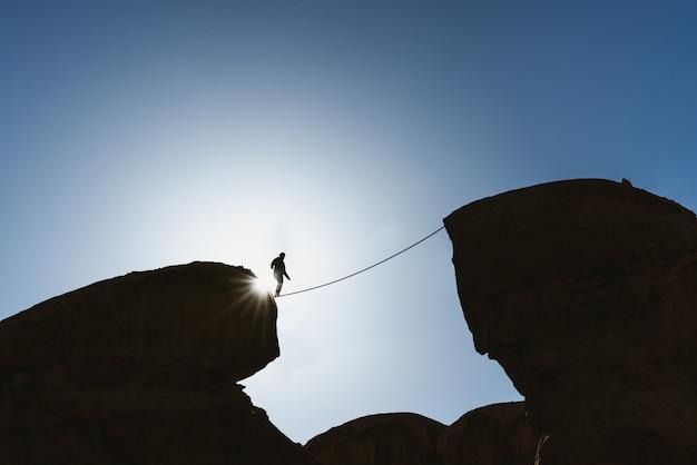 課題、リスク、集中力、そして勇気の概念。絶壁の上をロープで歩く人バランスをシルエットします。