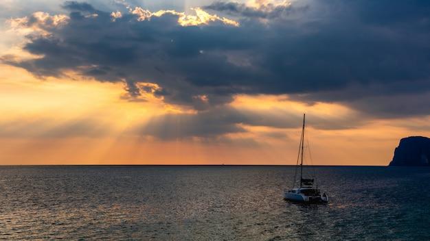 太陽の光は海のヨットで雲を通過します