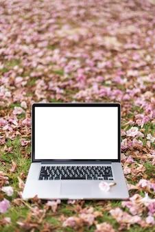 ピンクの花と緑の草の背景を持つラップトップコンピューター。垂直