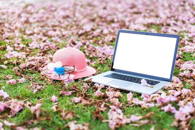 ラップトップコンピューターとピンクの花と緑の草の背景とピンクの帽子。
