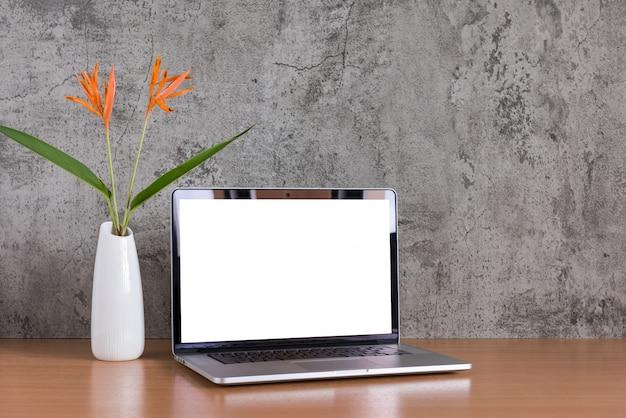花の花瓶とラップトップコンピューターの空白の画面