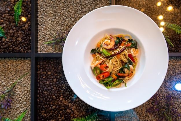 コーヒー豆のテーブルの上の白い皿にスパイシーなエビのスパゲッティ